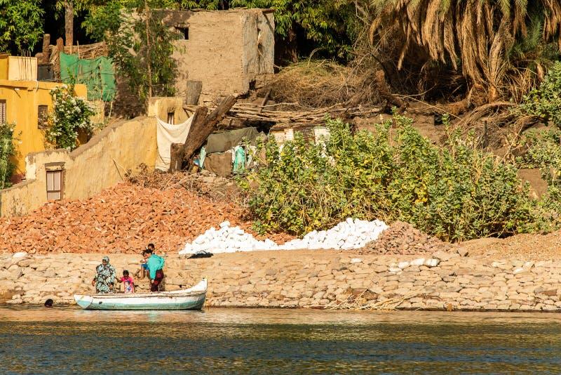 АСУАН, ЕГИПЕТ 21 05 Египетская семья 2018 работая на банке Нила стоковые фото