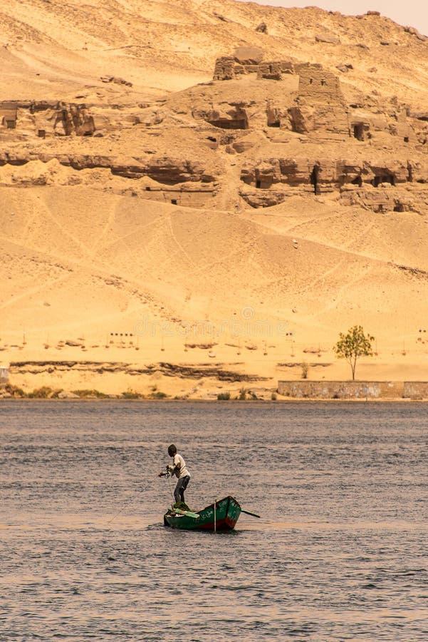 АСУАН, ЕГИПЕТ 21 05 Рыболов 2018 в его маленькой лодке удя в центре реки стоковое изображение rf