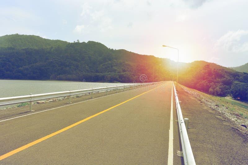 Асфальт-дорога с разделительной линией желтой полосы в центре на плотине стоковая фотография