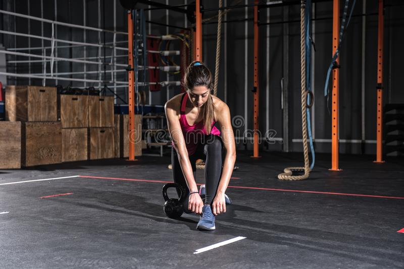 Атлетическая девушка готовая для того чтобы начать тренировки с kettlebell на спортзале стоковые изображения rf