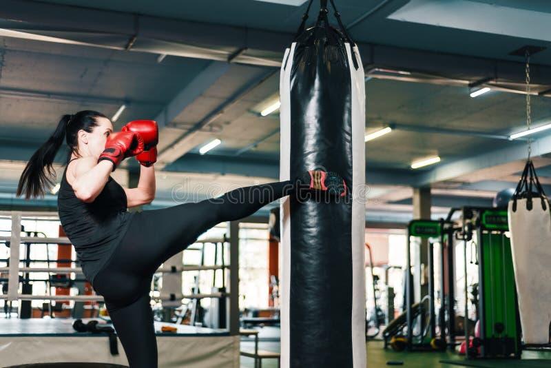Атлетическая девушка делает пинок на груше женщина в боевых искусствах поездов перчаток бокса стоковое фото rf