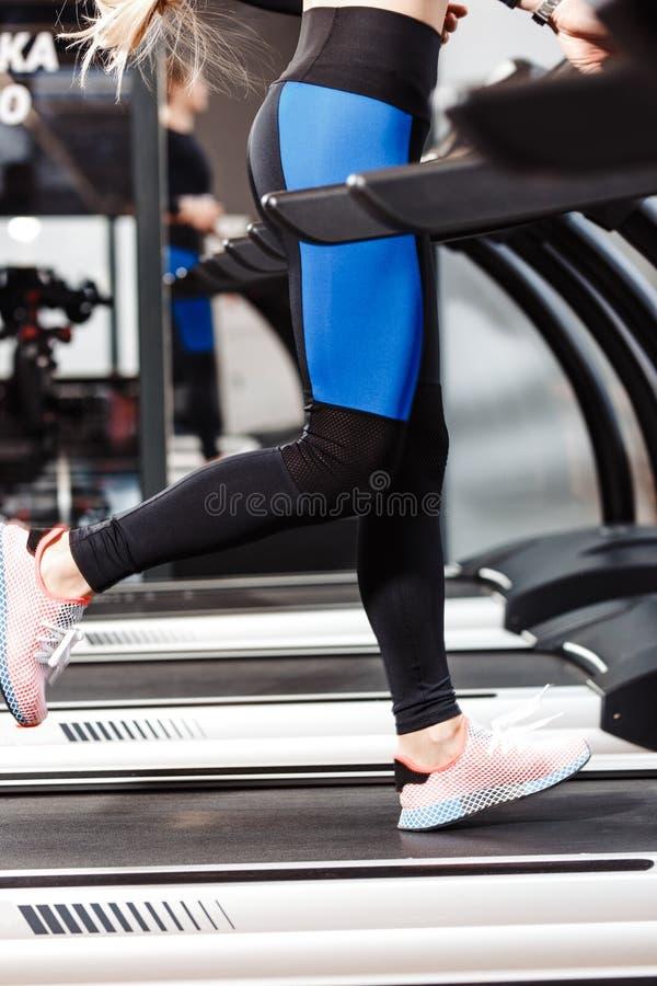 Атлетическая девушка одетая в sportswear бежит на третбане перед окнами в современном спортзале стоковое изображение rf