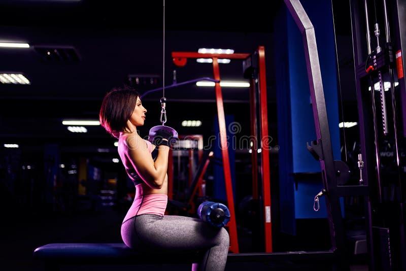 Атлетическая женщина делая тренировку для задней части, используя машину, в спортзале - заднем взгляде стоковое изображение