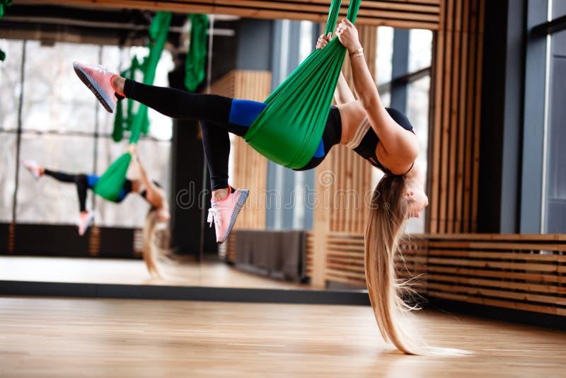 Атлетическая маленькая девочка с длинными светлыми волосами одетыми в одеждах спорта делает фитнес на зеленом воздушном шелке в стоковая фотография