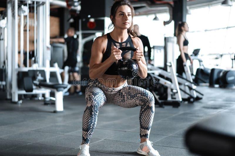 Атлетическая модель фитнеса молодой женщины делая сидения на корточках работает, образ жизни спорта концепции здоровый стоковые изображения rf