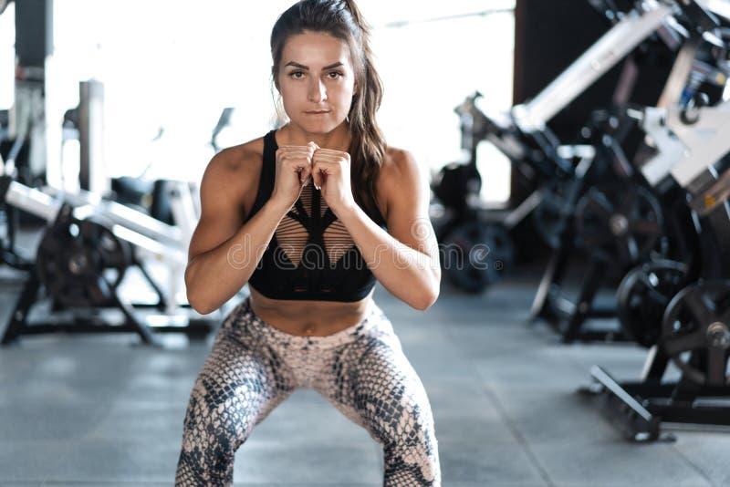 Атлетическая модель фитнеса молодой женщины делая сидения на корточках работает, образ жизни спорта концепции здоровый стоковое фото