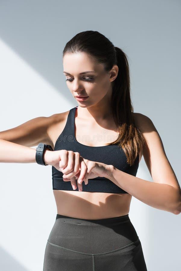 атлетическая молодая женщина в sportswear используя smartwatch стоковая фотография