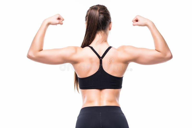 Атлетическая молодая женщина показывая мышцы задней части и рук на изолированной белой предпосылке стоковые фотографии rf