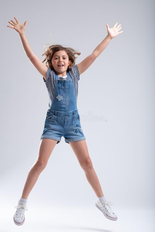Атлетическая худенькая маленькая девочка скача в воздух стоковые фото