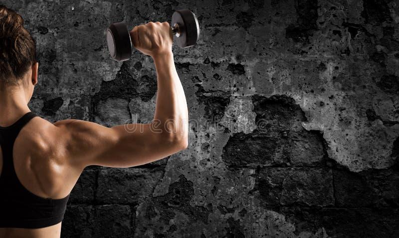 Атлетический бицепс тренировки женщины на предпосылке grunge стоковая фотография