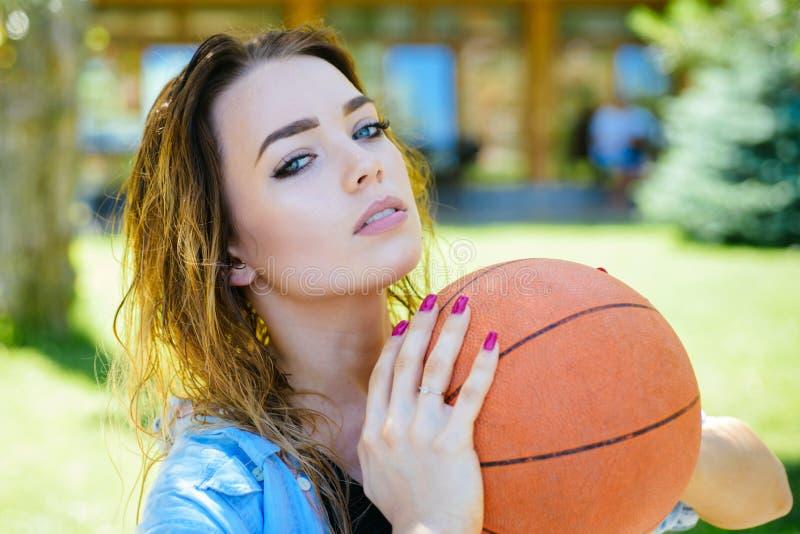 Атлетический и красивый Милая женщина с баскетболом Сексуальная женщина наслаждается тренировками шарика для тренировки спорта Же стоковые фотографии rf