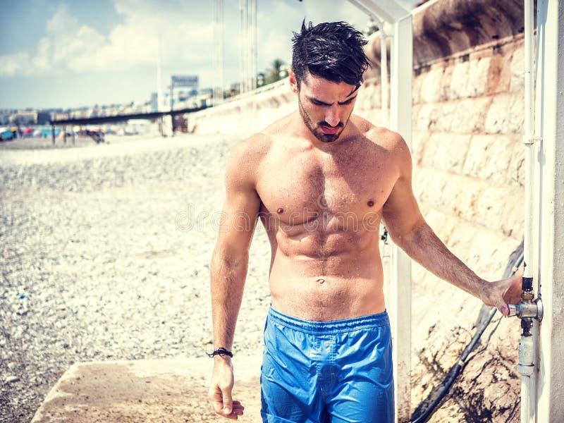 Атлетический молодой человек принимая ливень на пляже стоковое фото rf