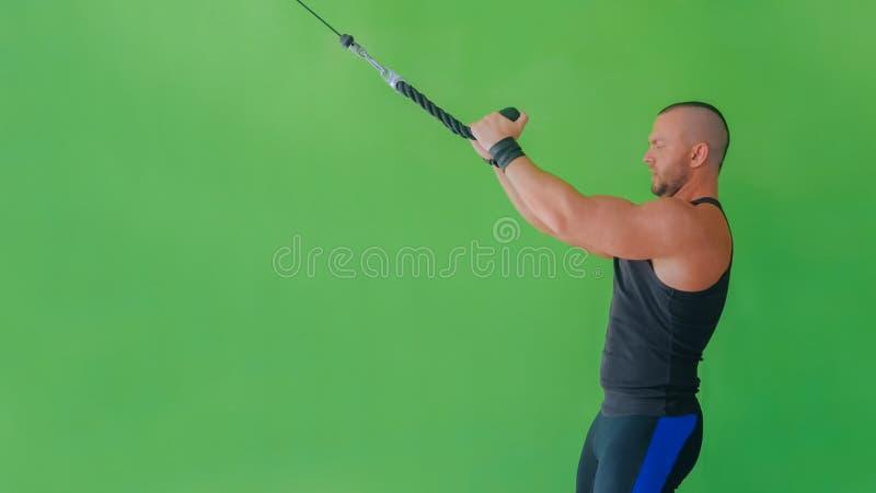 Атлетический молодой человек разрабатывая на оборудовании тренировки фитнеса на спортзале стоковые изображения rf