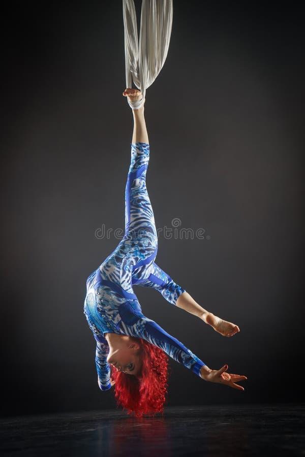 Атлетический сексуальный воздушный художник цирка с redhead в голубом костюме делая фокусы на воздушном шелке стоковые изображения rf