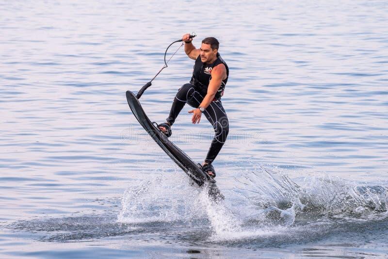 Атлетический человек на восхождении на борт воды - спорт в лете имея потеху на пляже стоковое фото rf