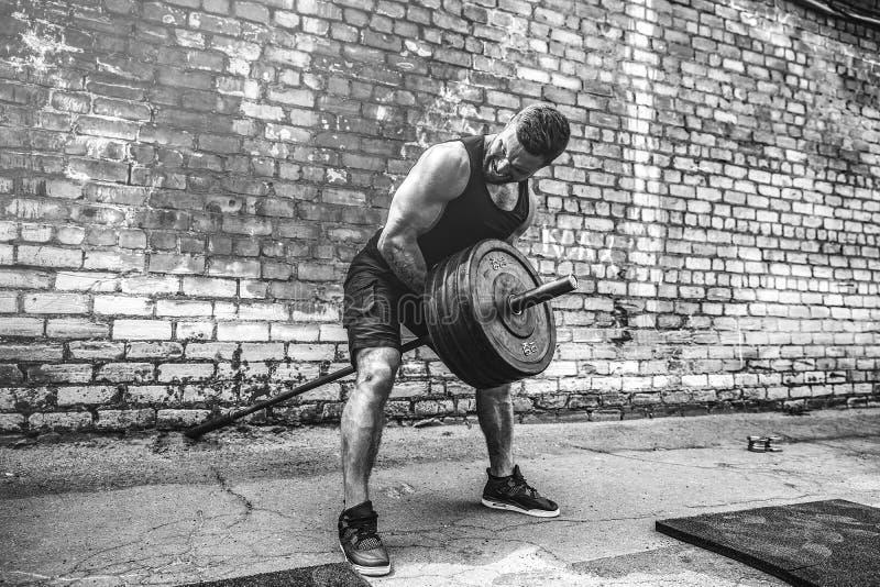 Атлетический человек разрабатывая с штангой Прочность и мотивировка Тренировка для мышц задней части стоковые изображения