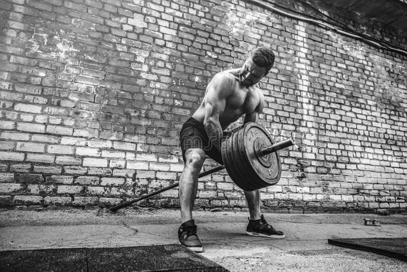 Атлетический человек разрабатывая с штангой Прочность и мотивировка Тренировка для мышц задней части стоковое фото rf