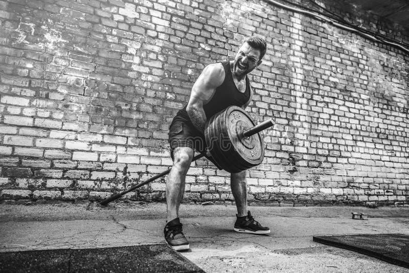 Атлетический человек разрабатывая с штангой Прочность и мотивировка Тренировка для мышц задней части стоковое изображение rf