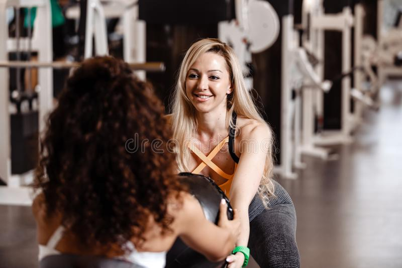 2 атлетических девушки одетой в sportswear делают совместно задние сидения на корточках с тяжелым шариком фитнеса в современном с стоковые изображения rf