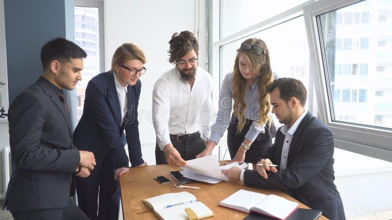 Атмосфера деятельности в офисе работники для того чтобы осмотреть документы в рабочем месте Группа в составе бизнесмены обсуждая стоковое фото