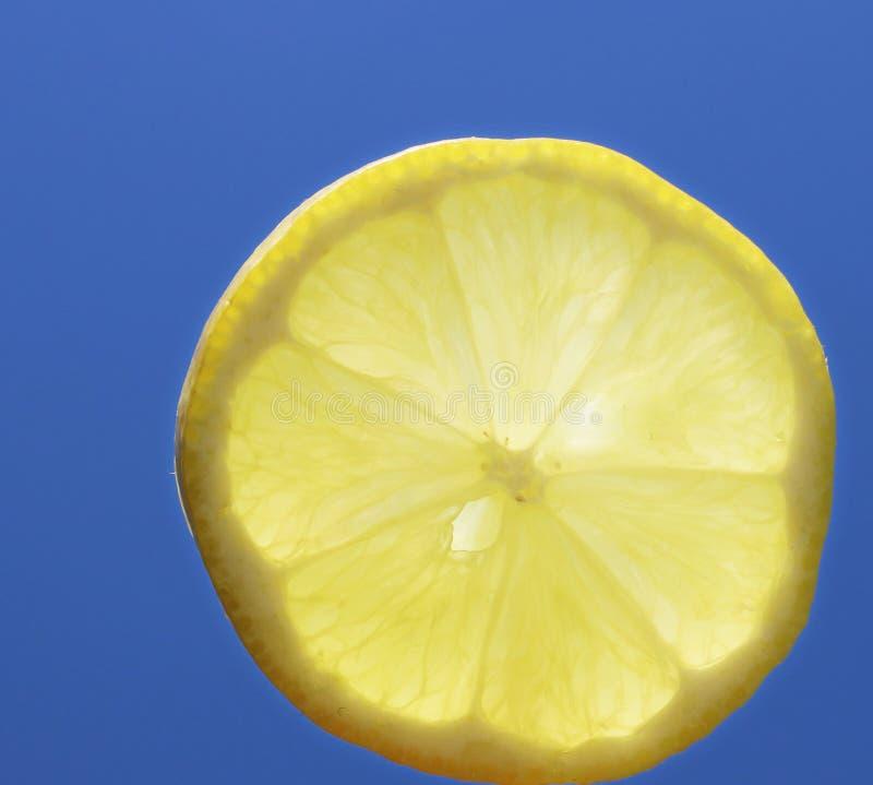Атмосфера каникул праздника с куском лимона перед солнцем и голубым небом стоковое фото