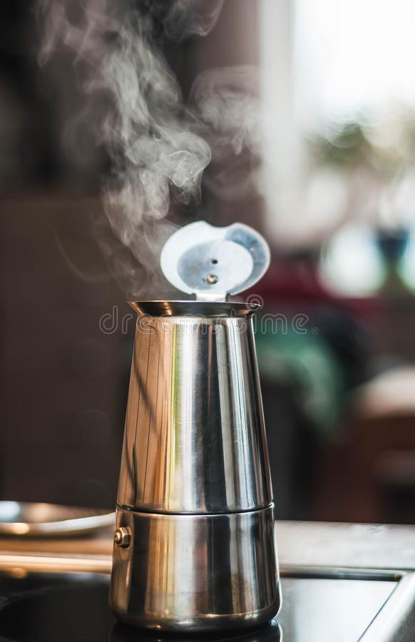 Атмосферическое теплое фото кофеварки на плите с кипя кофе и паром испаряться на расплывчатой предпосылке стоковые фото