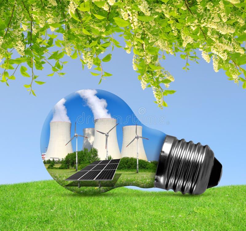Атомная электростанция с панелью солнечных батарей и ветротурбинами в лампочке стоковое фото