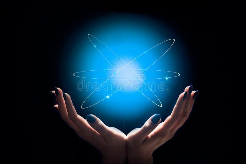 Атом в женских руках стоковая фотография rf