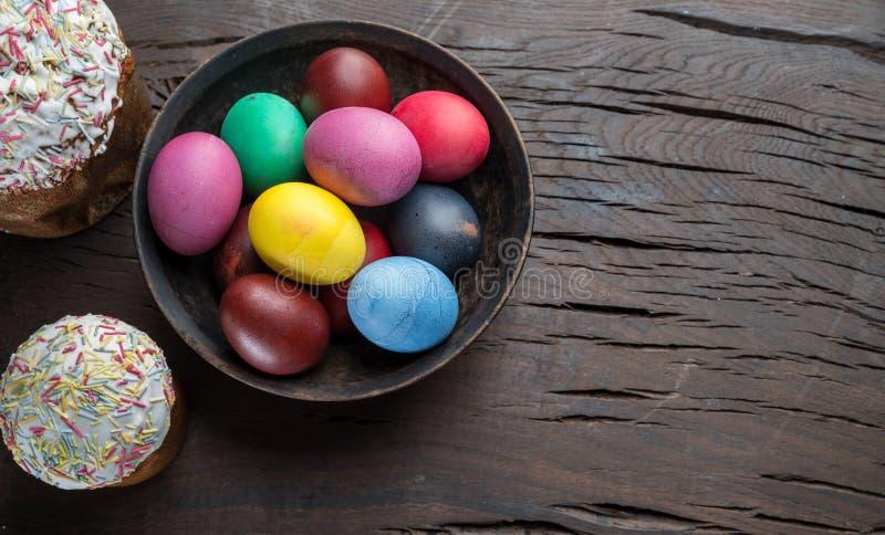 Атрибуты красочные пасхальные яйца и хлеб пасхи торжества пасхи Деревянная предпосылка стоковое изображение rf