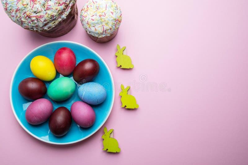 Атрибуты красочные пасхальные яйца и хлеб пасхи торжества пасхи Розовая предпосылка стоковые изображения rf