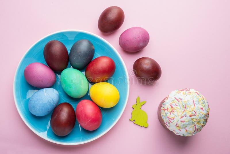 Атрибуты красочные пасхальные яйца и хлеб пасхи торжества пасхи Розовая предпосылка стоковое фото rf