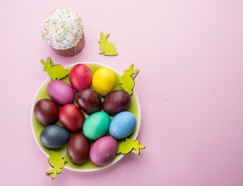 Атрибуты красочные пасхальные яйца и хлеб пасхи торжества пасхи Розовая предпосылка стоковая фотография