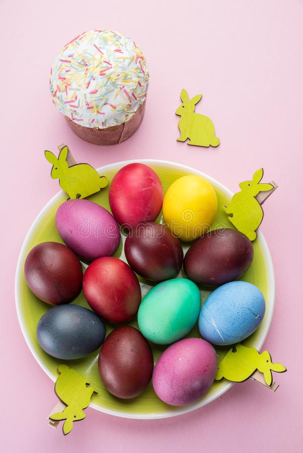 Атрибуты красочные пасхальные яйца и хлеб пасхи торжества пасхи Розовая предпосылка стоковая фотография rf