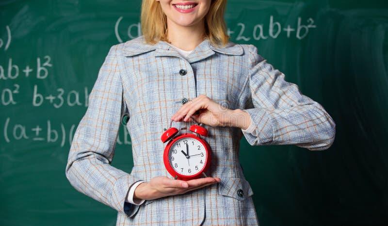 Атрибуты учителей Будильник в руках предпосылки доски класса учителя или воспитателя Дисциплина школы стоковая фотография rf