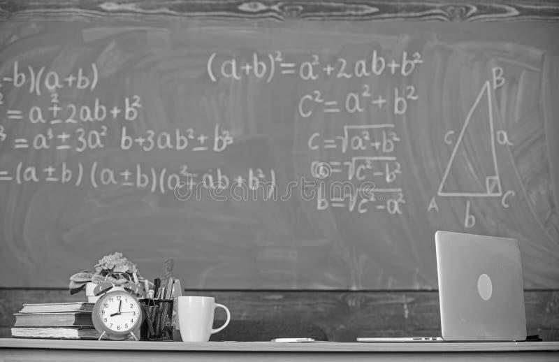 Атрибуты учителей Поставьте на обсуждение с книгами будильника школьных принадлежностей и предпосылкой доски класса кружки Работа стоковая фотография