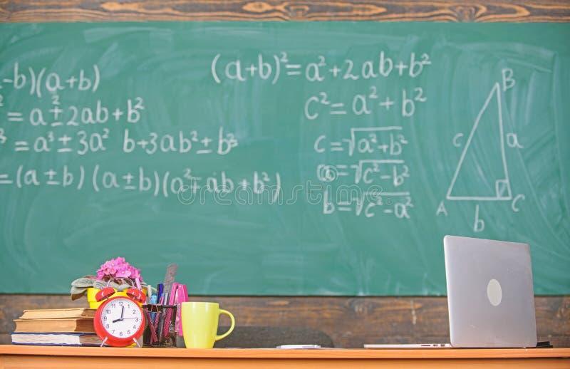 Атрибуты учителей Таблица с книгами будильника школьных принадлежностей и предпосылкой доски класса кружки Деятельность стоковые фото