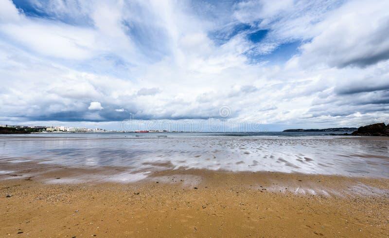 Атлантический песчаный пляж в Испании с городом предпосылки Coruna стоковое фото