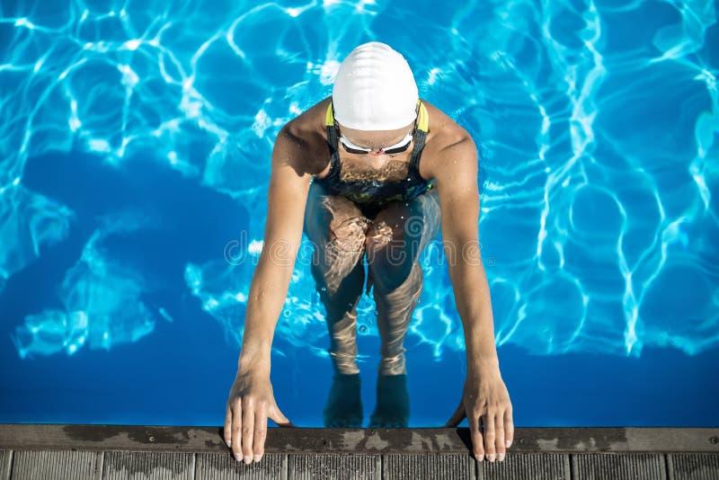Атлетическая девушка в бассейне заплыва стоковое фото