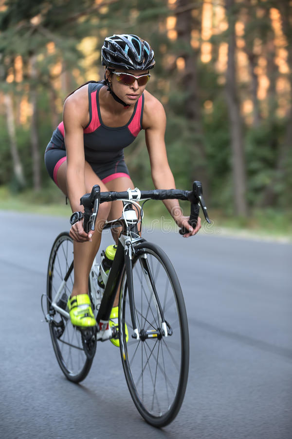 Атлетическая девушка едет велосипед стоковое изображение rf