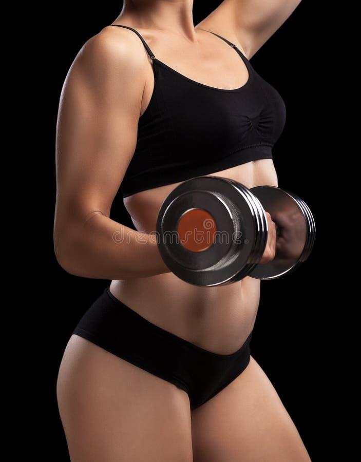 Атлетическая девушка с гантелями в руке стоковое фото rf