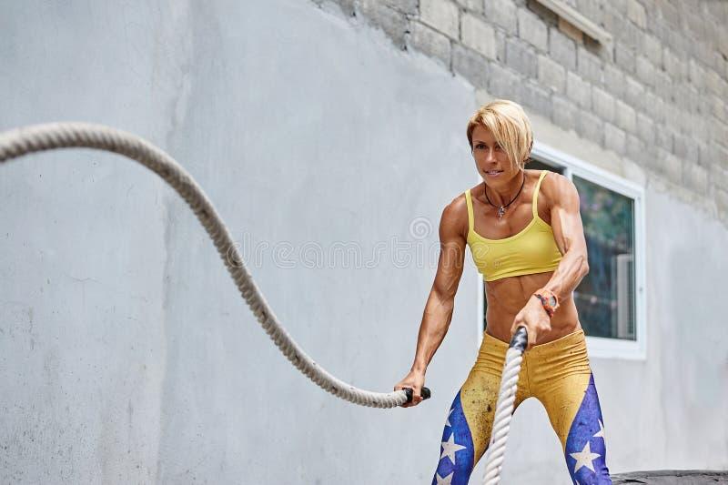Атлетическая женщина делая crossfit работает с веревочкой внешней стоковое изображение