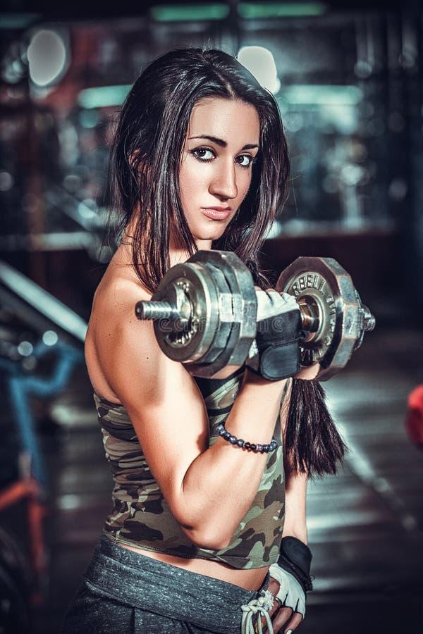 Атлетическая женщина нагнетая вверх muscules с гантелями стоковая фотография