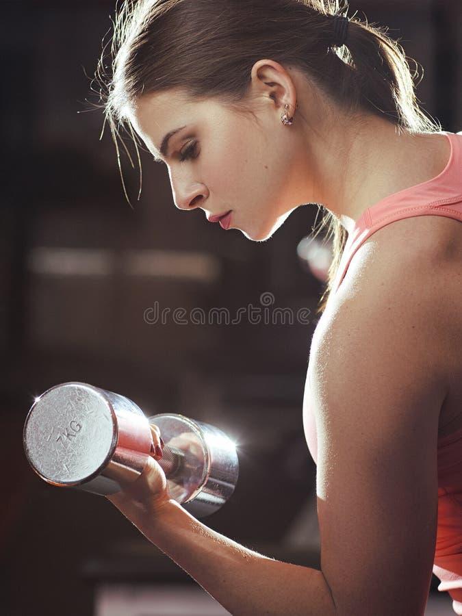 Атлетическая женщина нагнетая вверх muscules с гантелями стоковые изображения