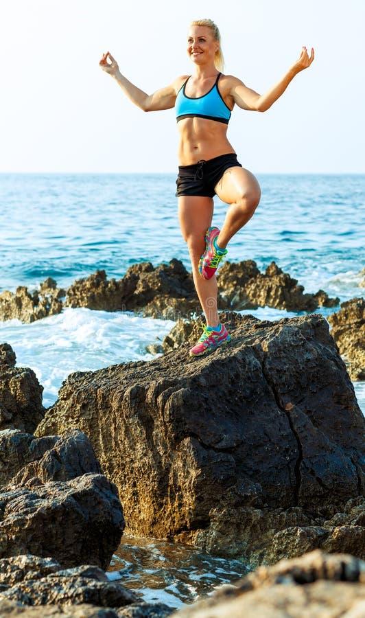 Атлетическая женщина ослабляя - практикуя йога на утесах se стоковые фотографии rf