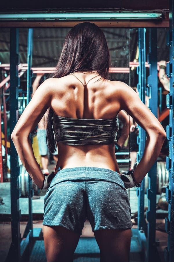 Атлетическая женщина показывая мышцы задней части стоковое изображение