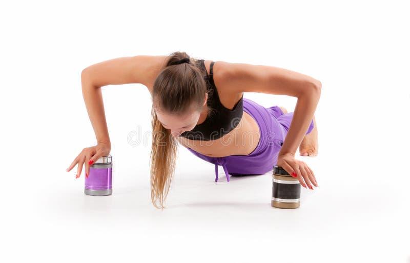 Атлетическая женщина разрабатывая на чонсервных банках изолированных BCAA и амино стоковое фото