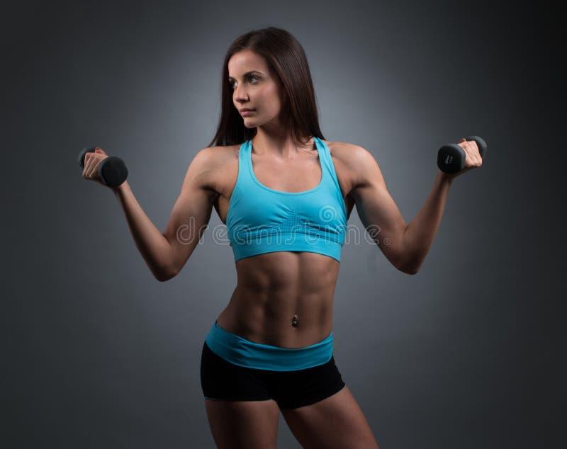 Атлетическая милая женщина поднимая 2 гантели стоковое фото