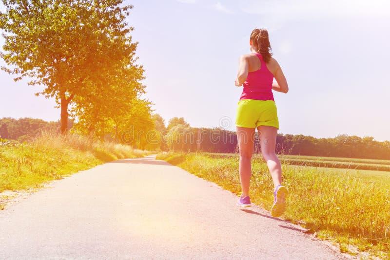 Атлетическая молодая женщина бежать outdoors во время осени стоковое изображение rf