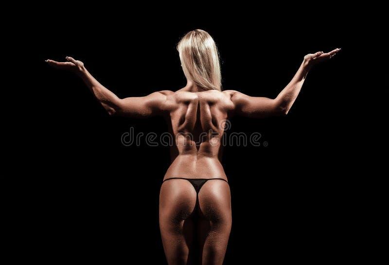 Атлетическая молодая женщина на изолированной черной предпосылке стоковое фото