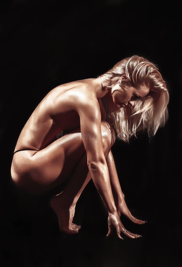 Атлетическая молодая женщина на изолированной черной предпосылке стоковые изображения